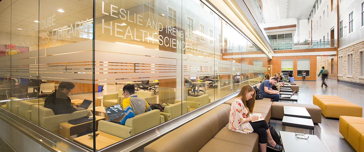 Students read by the Leslie and Irene Dubé Health Sciences Library at the University of Saskatchewan