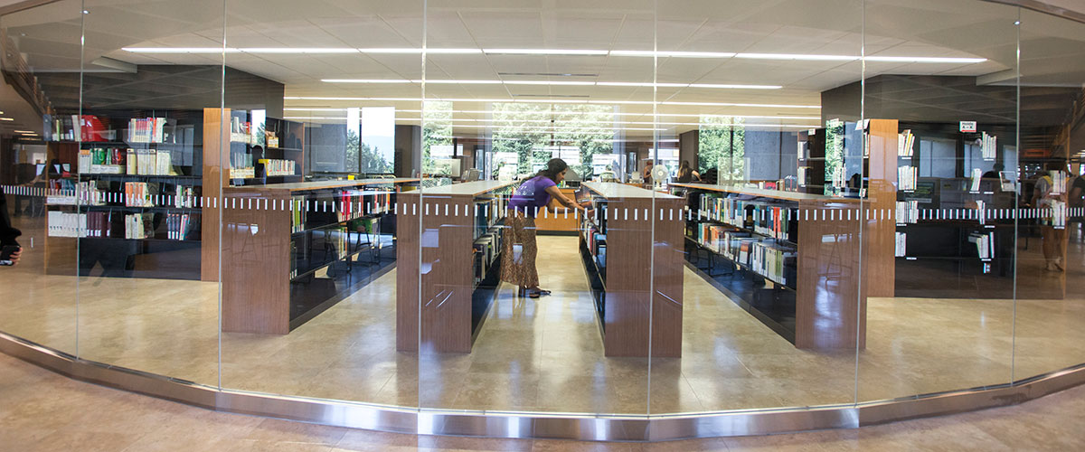 A library staff retrieves an item from the central reserves area in the Bennett Library at Simon Fraser University